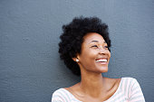 Close up portrait of smiling woman against gray wall