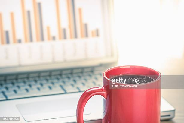 Close up still life of black coffee and bar finance chart on laptop screen