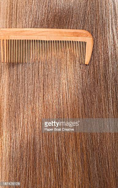 Close up straight brunette hair being combed