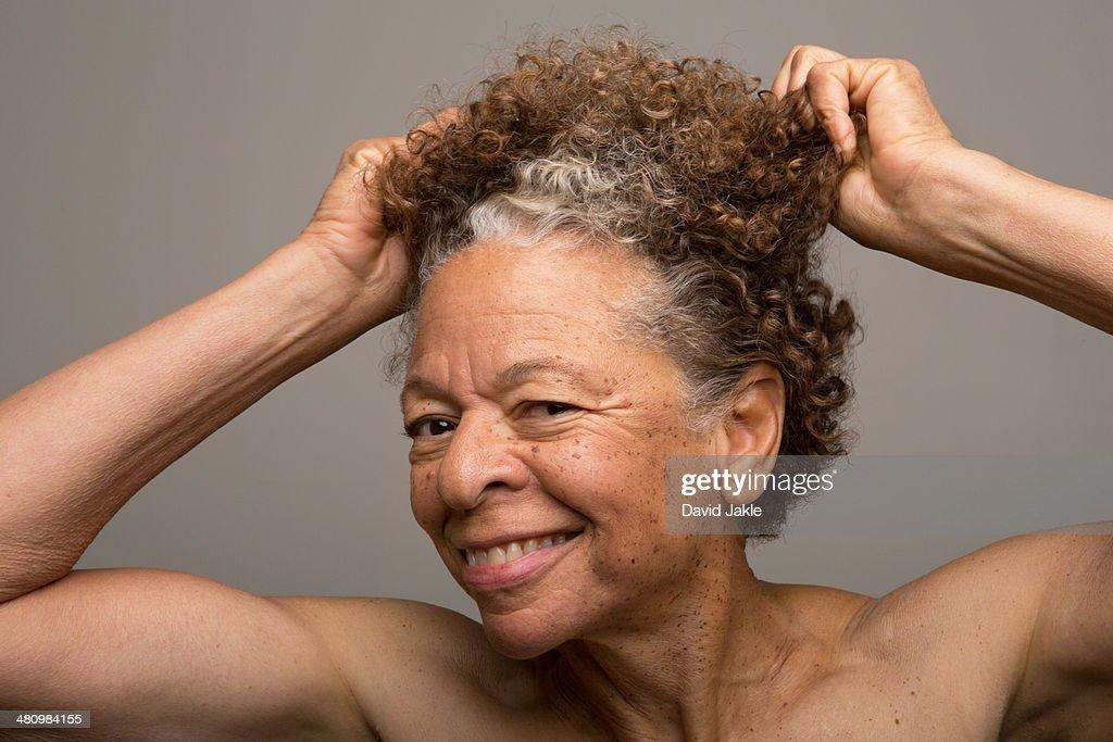 Close up studio portrait of senior woman pulling her hair : Stock Photo