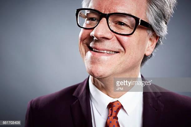 Close up studio portrait of smiling mature businessman