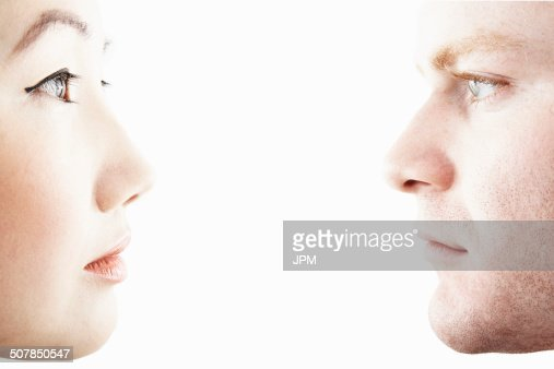 Close up studio portrait of young couple face to face in profile