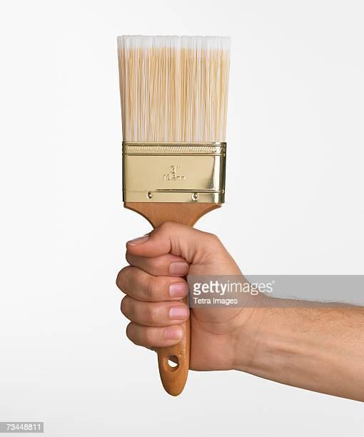 Close up studio shot of man holding paintbrush