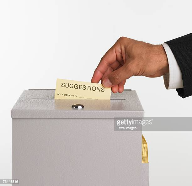 Close up studio shot of man putting card in suggestion box