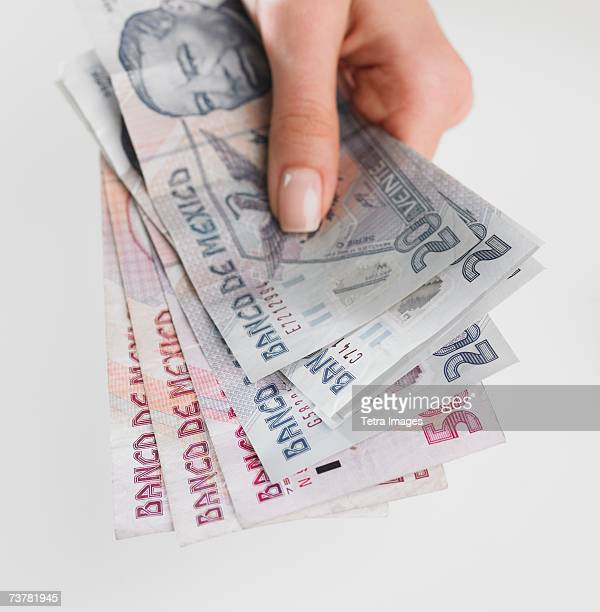 Close up studio shot of woman's hand holding Mexican money