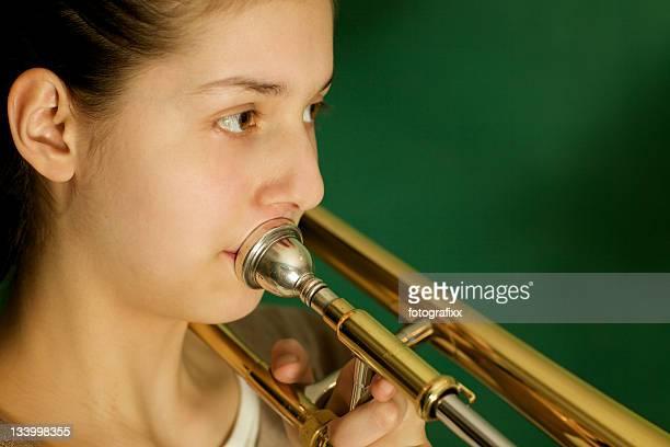 クローズアップ:吸うティーンエイジャーの女の子、トロンボーン練習