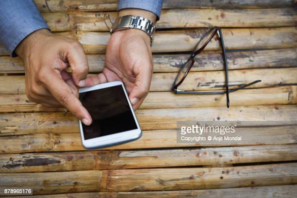Close up top view business man's hand holds smart phone with black isolated screen over wooden background