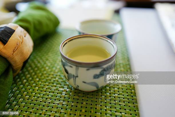 Close up view of a glass of Japanese sake rice wine on a woven mat with napkin and holder visible 2016