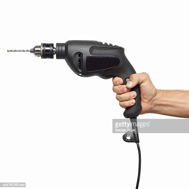 close up view of a hand holding a drill