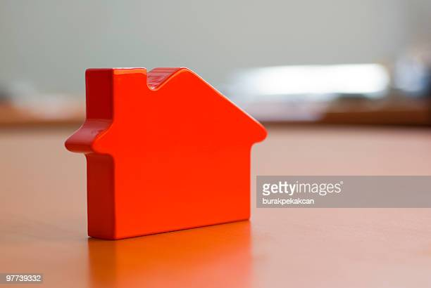 Close up view of a red plastic miniature house on a table