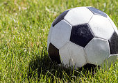 Close up view of a soccer ball or football on a green grassy field.