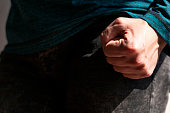 Close up view of Caucasian man's fist under strong natural sunlight with the rest of the body in shadow