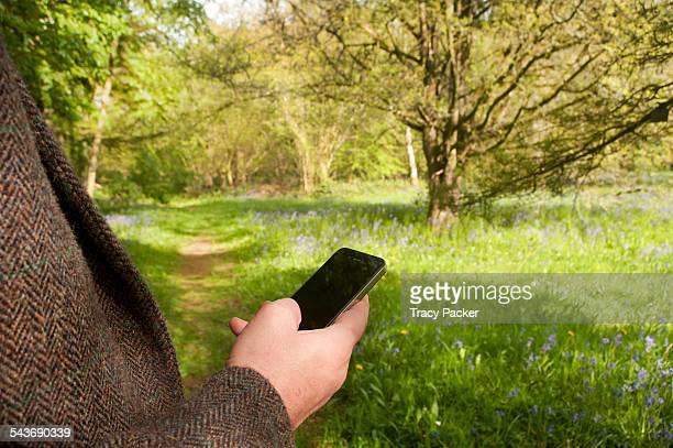 A close up view of the arm hand of a Caucasian man wearing a tweed jacket and holding a smartphone trying to get a mobile signal in a woodland area