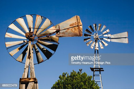 Close up view of two old windmills standing in the yard of a farm : Stock Photo