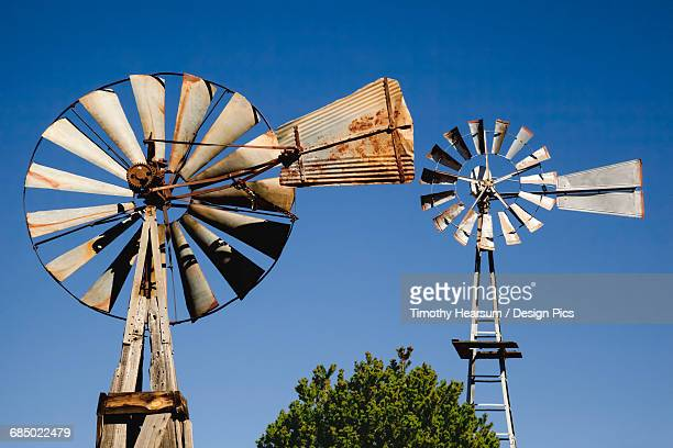 Close up view of two old windmills standing in the yard of a farm