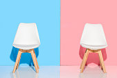 close up view of white chairs against blue and pink wall