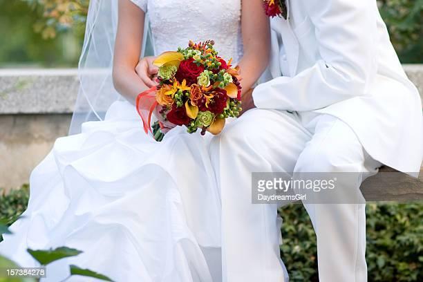 Gros plan de Couple habillé en blanc tenant un Bouquet de fleurs