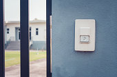 Close up white doorbell or buzzer button on concrete wall beside doorway with house in the background.
