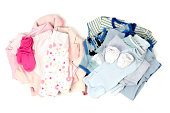 Close up with a blue stack of clean baby clothes for a boy and a pink clean babby clothes for a girl isolated on white