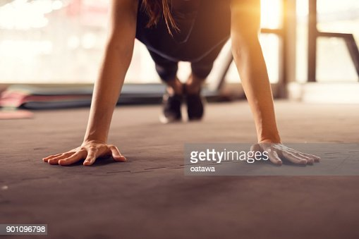 Close up woman hand doing push ups exercise in a gym in morning, sunlight effect. : Stock Photo