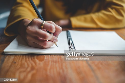 Close up woman hand writing on notebook : Foto de stock