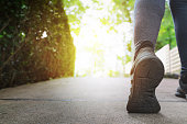 Close up woman running shoes, jogging on the road in a park, sport and health lifestyle concept