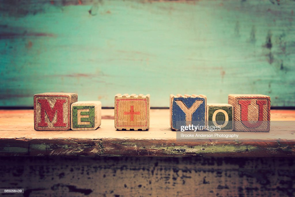 Close up wooden block letters spelling ME + YOU