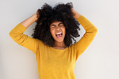 Close up portrait of young african girl screaming and pulling her hair against white background