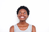 Close up portrait of young african woman looking up and smiling on white background