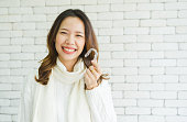 close up young asian woman smiling with hand holding dental aligner retainer (invisible) at dental clinic for beautiful teeth treatment course concept