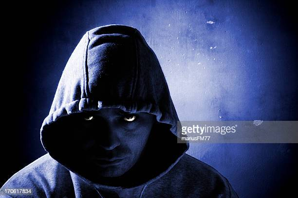 Close view of a dangerous man wearing hooded jacket at night