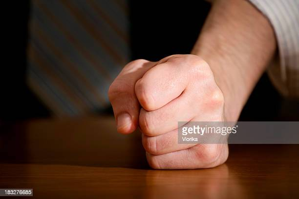 A closed fist on a shiny wooden table