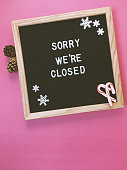 """A letter board displaying the message """"Sorry we're closed"""". Candy canes and Snowflake accents for a holiday business closed sign. Indoor studio flat lay."""