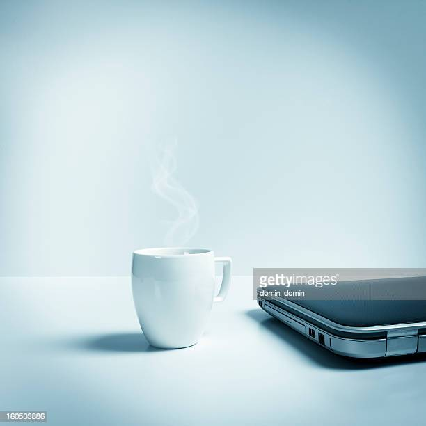 Closed laptop with mug of hot tea, coffee, blue toned