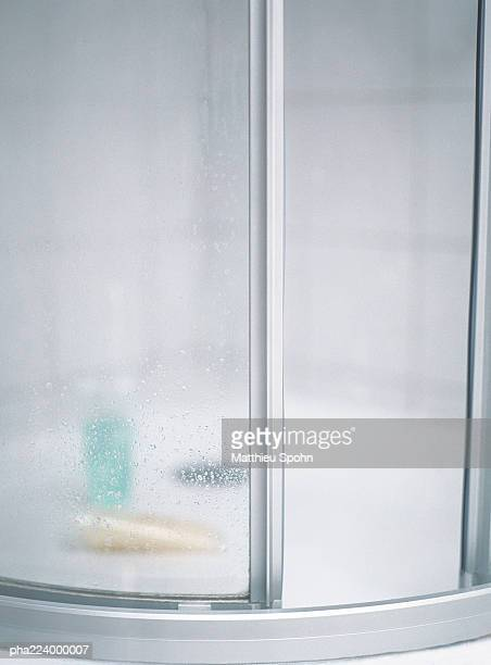 Closed shower doors, blurred bottles inside.