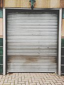 Closed Shutter Of Store At Sidewalk