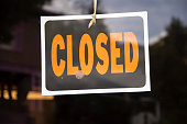 Closed sign hanging in business window by a string - crooked with glob of glue also attaching it to window - some abstract reflections