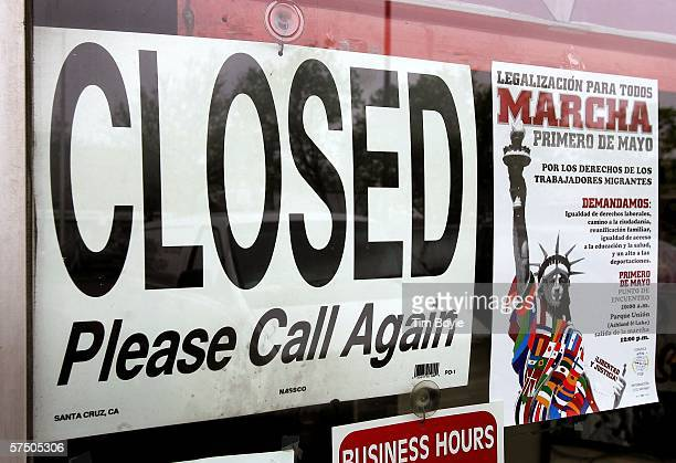 A closed sign in is visible in a store window next to a promotional poster for the 'Marcha' in Spanish May 1 2006 in Mount Prospect Illinois...
