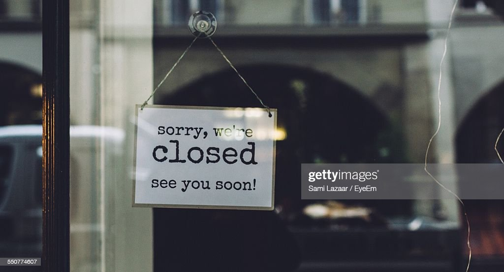 Closed Sign On Glass Wall Of Store