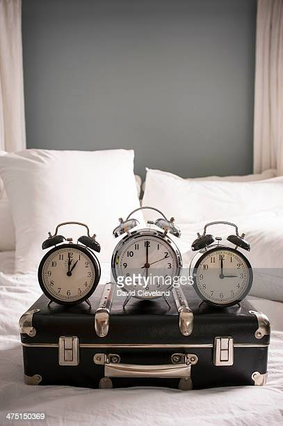 Closed suitcase on bed with three alarm clocks