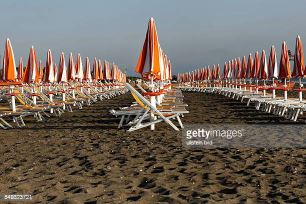 Closed sun umbrellas and deck chairs without people on a Italian beach Bibbona Tuscany Italy