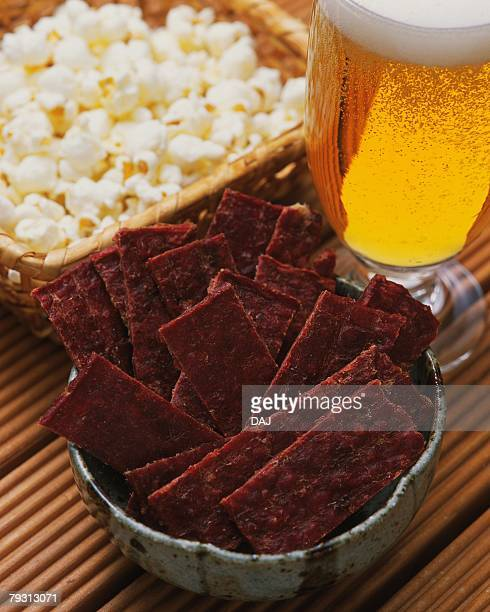 Closed Up Image of a Little Bowl Filled With Beef Jerky, and a Wooden Basket Filled With Popcorn Next to a Glass of Beer, High Angle View