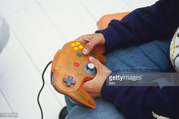 Closed Up Image of a Little Child's Hand Holding a Video Game Controller, High Angle View