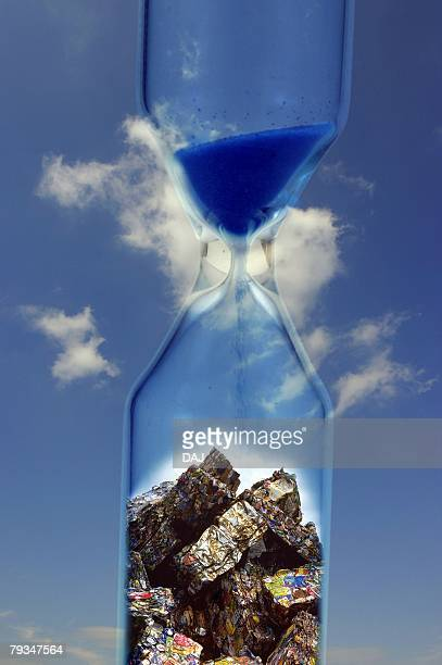 Closed Up Image of a Sandglass With Blue Sand and Some Industrial Waste in It, In Front of a Blue Sky, CG