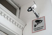 Closed-circuit television, surveillance camera on building exterior. Sign in German language ´This area is video monitored´