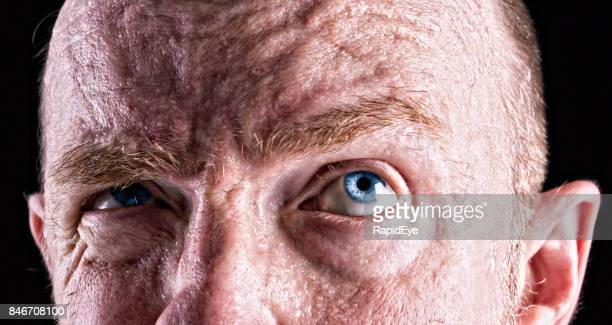 Close-op of mature man with very blue eyes looking up