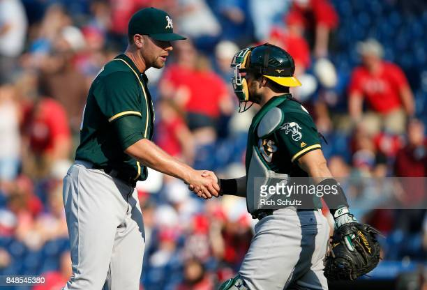 Closer Blake Treinen shakes hands with catcher Josh Phegley of the Oakland Athletics after defeating the Philadelphia Phillies 63 during a game at...