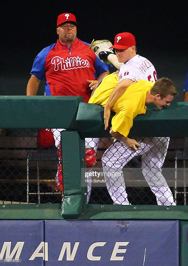 Closer <a gi-track='captionPersonalityLinkClicked' href=/galleries/search?phrase=Jonathan+Papelbon&family=editorial&specificpeople=453535 ng-click='$event.stopPropagation()'>Jonathan Papelbon</a> #58 of the Philadelphia Phillies wrestles with a fan who jumped into the bullpen after running on the field in the seventh inning during a MLB baseball game against the Atlanta Braves on July 7, 2012 at Citizens Bank Park in Philadelphia, Pennsylvania.