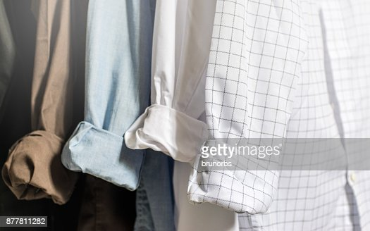 Closet wardrobe interior, showing men's dress shirts with folded and cuffed cuffs, white, blue, brown and black shirts, with light tones and soft focus : Stock Photo