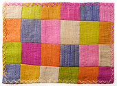 Closeup at colorful patchwork table mat , striped texture background.